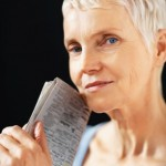 Closeup of a aged lady holding newspaper